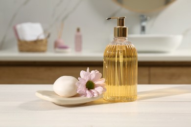 Glass dispenser with shower gel, soap bar and flower on white table in bathroom