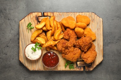 Tasty fried chicken nuggets served on grey table, top view