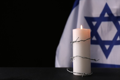 Barbed wire and burning candle on black background, space for text. Holocaust memory day