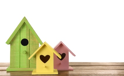 Three different bird houses on wooden table against white background