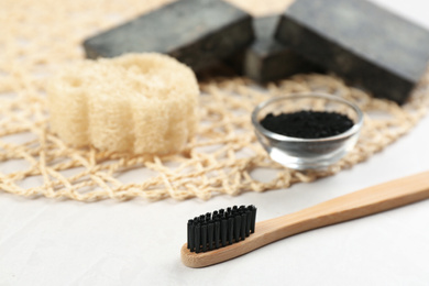 Bamboo toothbrush on white table, closeup. Space for text