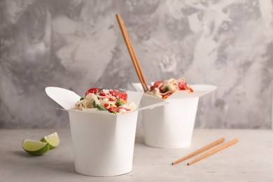 Boxes of vegetarian wok noodles with chopsticks on light table