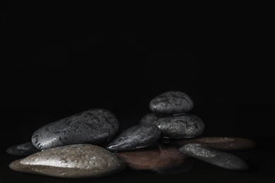 Stones in water on black background, space for text. Zen lifestyle