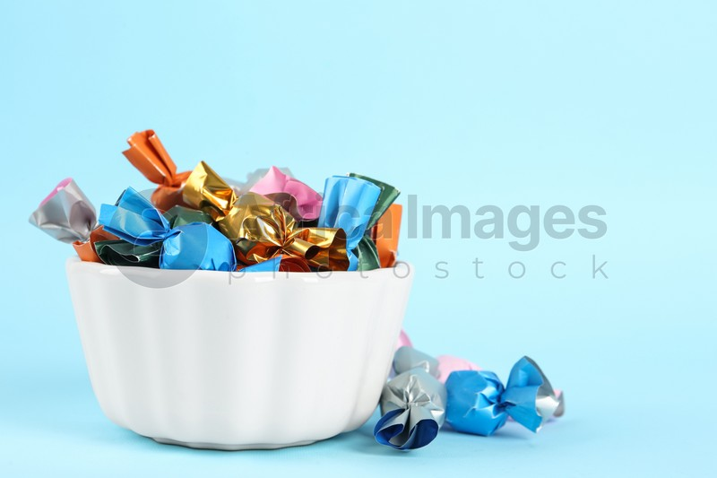 Candies in colorful wrappers on light blue background, space for text