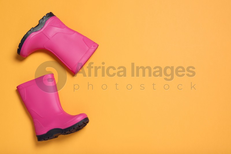 Pair of bright pink rubber boots on orange background, top view. Space for text