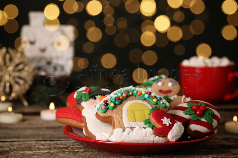 Sweet Christmas cookies on wooden table against blurred festive lights. Space for text
