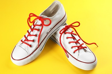 Pair of trendy sneakers on yellow background