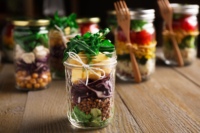 Glass jar with healthy meal on wooden table