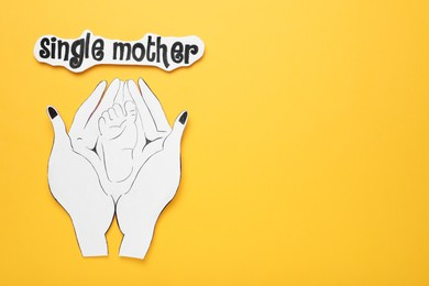 Being single mother concept. Woman holding her baby's feet made of paper on orange background, flat lay and space for text