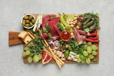Set of different delicious appetizers served on light grey table, top view
