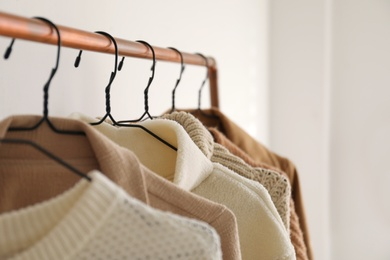 Rack with stylish women's clothes indoors, closeup. Modern interior design