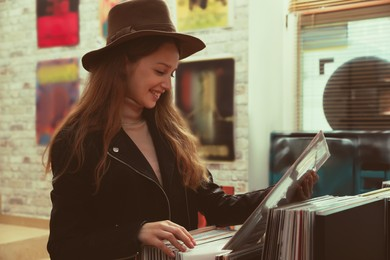 Young woman with vinyl record in store