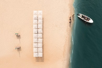 Motorboat near sandy coast with beach umbrellas, aerial view. Summer vacation
