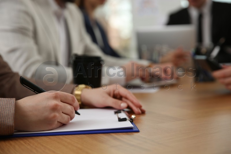 Woman writing at table during business meeting, closeup. Management consulting