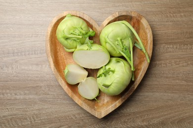 Whole and cut kohlrabi plants on wooden table, top view