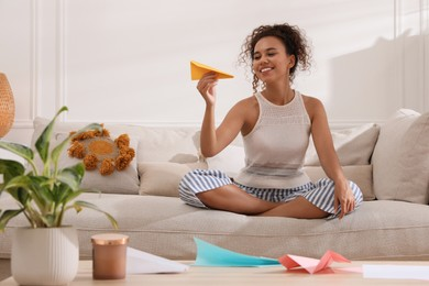 Beautiful African-American woman playing with paper plane in living room at home