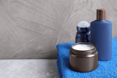 Cosmetic products and towel on light grey marble table, space for text. Men's hygiene