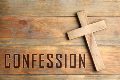 Christian cross and word Confession on wooden background, top view