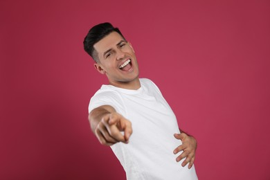 Handsome man laughing on maroon background. Funny joke