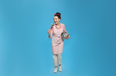 Housewife with pan and ladle on light blue background