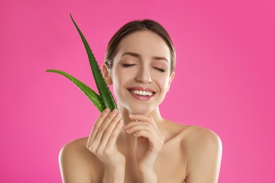Happy young woman with aloe leaves on pink background