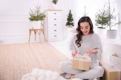Woman with gift box on floor at home. Space for text