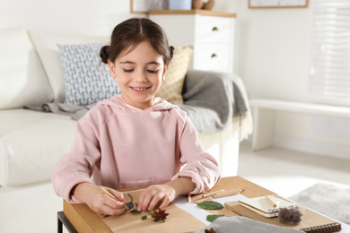 Little girl working with natural materials at table indoors. Creative hobby