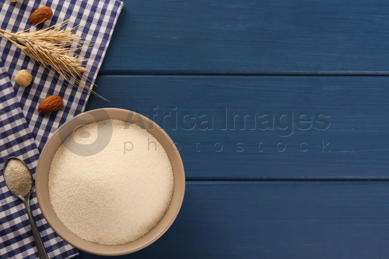 Uncooked organic semolina with spikelets and nuts on blue wooden table, flat lay. Space for text