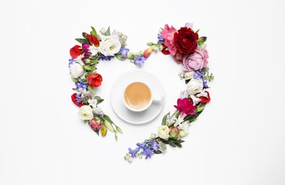 Beautiful heart made of different flowers and coffee  on white background, top view
