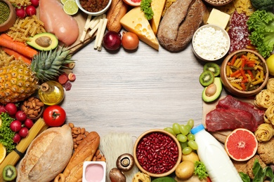 Frame made of different food products on wooden table, flat lay with space for text. Healthy balanced diet