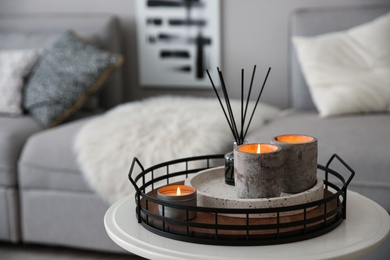 Candles and aroma reed diffuser on white table near grey sofa