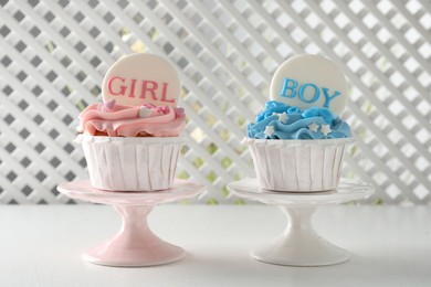 Delicious cupcakes decorated with Girl and Boy toppers for baby shower on white table