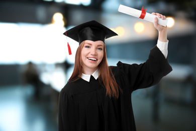 Happy student with graduation hat and diploma in office