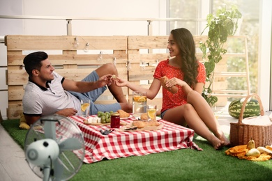 Happy couple with tasty food imitating picnic at home