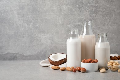 Different nut milks on light grey table. Space for text
