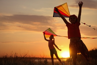 Cute little children playing with kites outdoors at sunset. Spending time in nature