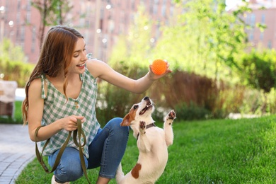 Young woman playing with adorable Jack Russell Terrier dog outdoors