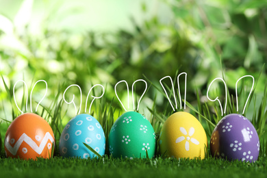 Bright Easter eggs with cute bunny ears in green grass