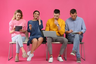 People waiting for job interview on pink background