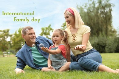 Happy parents and their daughter blowing soap bubbles in park on green grass. Happy Family Day