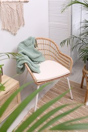 Stylish room interior with beautiful potted plants and comfortable chair