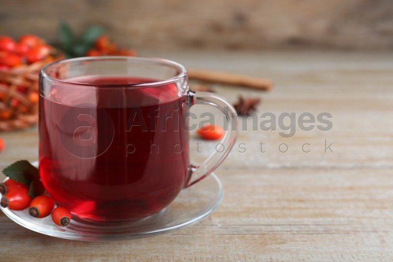 Aromatic rose hip tea and fresh berries on wooden table, space for text
