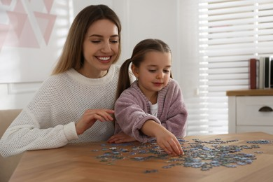 Woman and his little daughter playing with puzzles at home