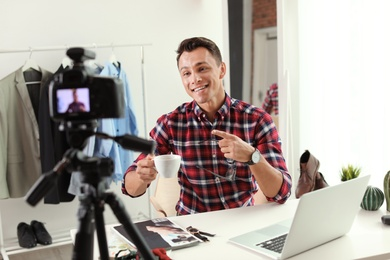 Fashion blogger with cup of coffee recording video on camera at home