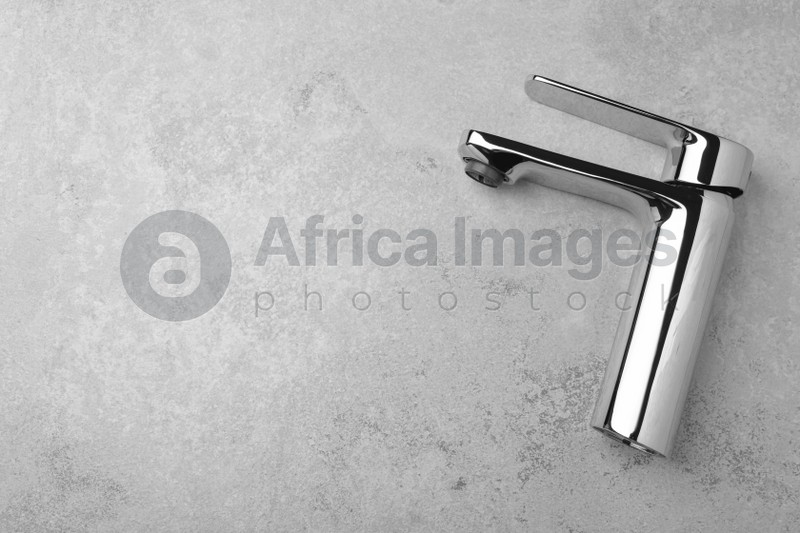Single handle water tap on grey table, top view. Space for text