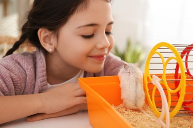Little girl and her hamster in cage at home
