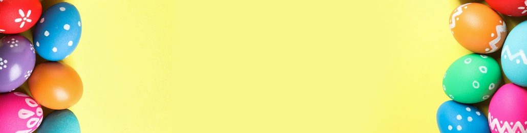 Colorful Easter eggs and space for text on yellow background, flat lay. Horizontal banner design