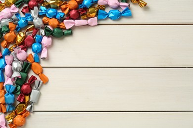 Candies in colorful wrappers on beige wooden table, flat lay. Space for text