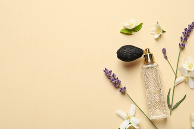 Flat lay composition with elegant perfume and beautiful flowers on beige background, space for text