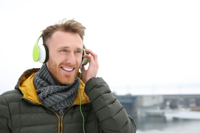 Young man listening to music with headphones outdoors. Space for text
